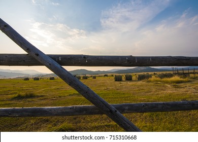 landscape of hay bales in Montana  at sunset with an old fence with blue skies and clouds