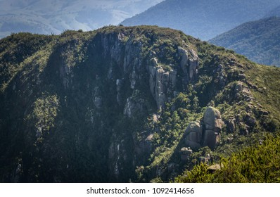Landscape of a high mountain with green nature and rocks visible in Brazil with clouds near the peaks.