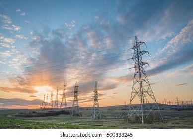 Landscape with high-voltage power lines. Electricity distribution station. High voltage electric transmission tower at sunset. Bulgaria