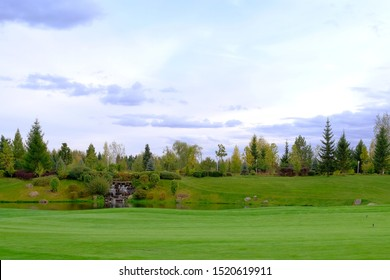 Landscape. Hills with green lawn and ornamental shrubs, trees, lake and waterfall. It's a beautiful garden.