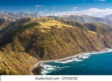 landscape with hills, ocean and wind turbines