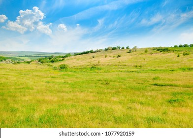 Landscape with hilly field and blue sky. Agricultural landscape.