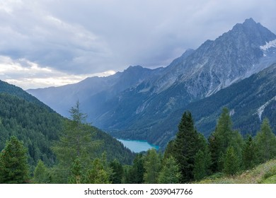 Landscape of Hochgall mountain peaks covered by clouds, valley and Antholzer See lake in Dolomites, Italy, travel and nature concept