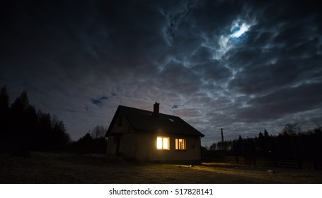 Landscape with house at night under cloudy sky. Spooky landscape with house in night.