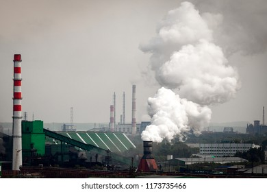 The landscape of a huge industrial city with factories and high cranes from which come out with huge smoke puffs. Pollution of the environment by plants and industries