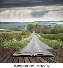 Landscape image of empty road in English countryside with stormy sky overhead concept coming out of pages in open book