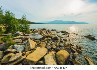 Landscape with the image lake Baikal and the mountains in Buryatia. Warm sunny day in Siberia. Crystal clear water of lake Baikal. Summer relax on the widely known and popular lake Baikal.