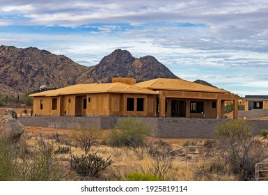 Landscape image of a large custom home being built in North Scottsdale AZ with Mcdowell Mountains in Background.