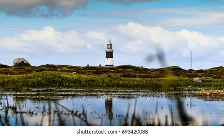 Landscape image of the Lighthouse on Tory Island Donegal Ireland.  A reflection of the lighthouse in the water.