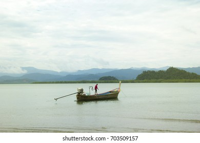 Landscape Image of long-tailed boat for fishing of fishermen inhabiting the west coast andaman sea of Ranong Province Thailand. In an atmosphere surrounded by mountains sea water cloud and sky.