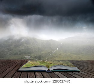 Landscape image of low cloud hanging over Snowdonia mountain range after heavy rainfall in Autumn with misty weather coming out of pages of open story book
