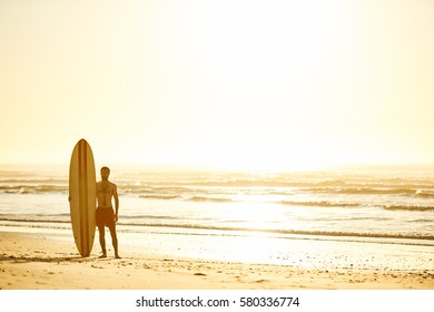 Landscape image of male surfer posing with his surfboard standing upright beside him on the beach with the waves breaking in the background and the sun coming up over the ocean.