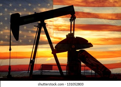 Landscape image of a oil well pumpjack wiith an early morning golden sunrise and American USA red White and Blue Flag background.