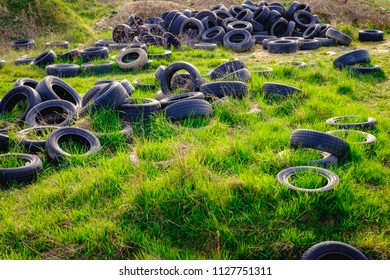 Landscape image of polluted environment with old used car tyres