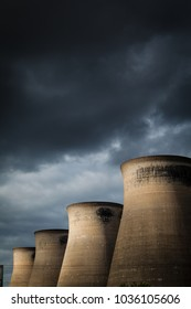 Landscape image of a power stations cooling towers with a moody overcast sky
