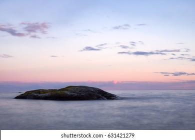 Landscape image of rock in water during pastel sunset in the Stockholm Sweden archipelago