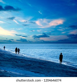 Landscape image of silhouetted people walking on sandy beach in morning over cloudy sky