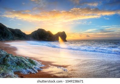 Landscape image of sunrise shining through the arch of Durdle Door on the Jurassic Coast