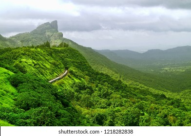 Landscape Image of a train passing through the tunnel that has been carved through the beautiful landscape of the mountains on the Mumbai Pune railway track in the Indian state of Maharashtra