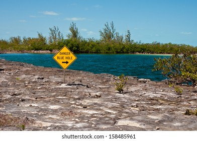 Landscape image of a yellow danger sign warning about a blue hole  in the islands of the bahamas.