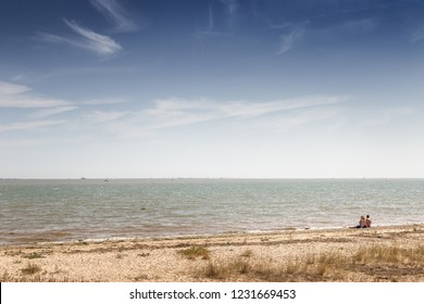 landscape images taken from a walk around the island of east mersea in essex england with two people sitting on the beach looking out to sea