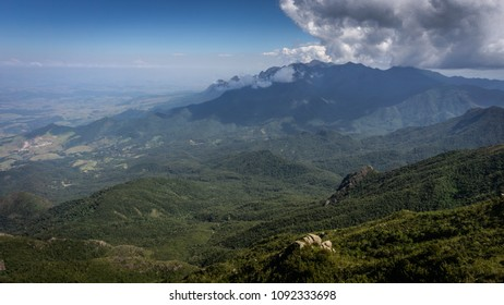 Landscape of the imposing mountain range in the background, reaching the clouds and a green nature valley illuminated by the blue sky in Brazil.