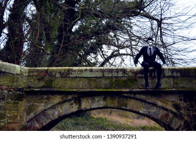 Landscape of 'invisible' man in a smart suit located in forestry area and on essex bridge located in Great Haywood, Stafford, England.