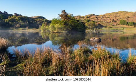Landscape with island and mountains reflecting in calm water misty morning sunrise on lakeside of Rydal Water, Lake District, England