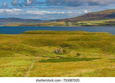 Landscape of the Isle of Skye in Scotland with a crumbling cottage in the middle of a field.