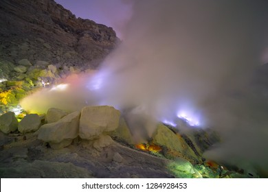 Landscape of Kawah Ijen volcano crater with blue flame and sulfuric smoke view with sunrise dawn morning in East Java, Indonesia
