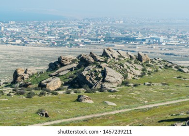 Landscape in Kichikdash area of Gobustan, Azerbaijan, with boulder stacks and Gobustan settlement in the background.