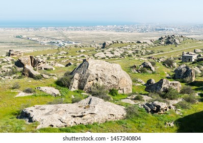 Landscape in Kichikdash area of Gobustan, Azerbaijan, with boulder stacks and Gobustan prison and settlement in the background.