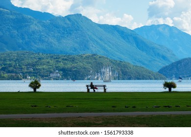 Landscape with lake Annecy and the Alps in September. The mountains are covered with a light, steinate haze. The atmosphere of relaxation and tranquility. A woman sits on a bench in the distance. Scen