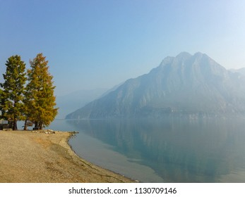 Landscape of lake shore with trees on mountains reflecting in sea water background on blue sky in sunny scenic view of serene tranquil scenery, nature travel concept. Italy, Lombardia, Riva di Solto