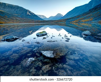 Landscape of lake Tahtarjavr with transparent water, rocky bottom and distant mountains reflected in still morning waters, Hibiny mountains above the Arctic circle, Russia