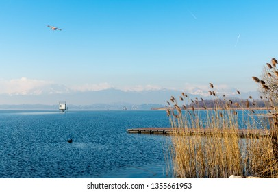 Landscape of Lake Varese on a winter day, with the plane flying over and mountains with snow covered peaks in background.