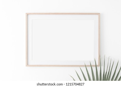 Landscape large 50x70, 20x28, a3,a4, Wooden frame mockup with passe-partout on white wall and palm leaf. Poster mockup. Clean, modern, minimal frame. Empty fra.me Indoor interior, show text or product
