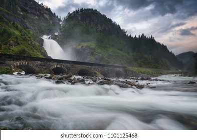 Landscape with Latefossen waterfall, river stream and stone bridge near Odda, Norway