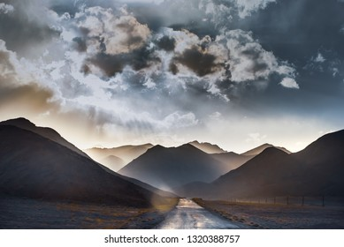 Landscape of layered mountains. Silhouettes of mountains in the rays of the setting sun. The road in the mountains - soft focus, noise, artifacts, film grain.