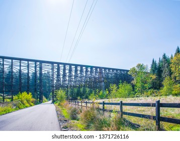 Landscape with a local road passing through the valley under a unique old build existing Holcomb creek wooden train trestle, allowing simultaneous movement along it in only one direction