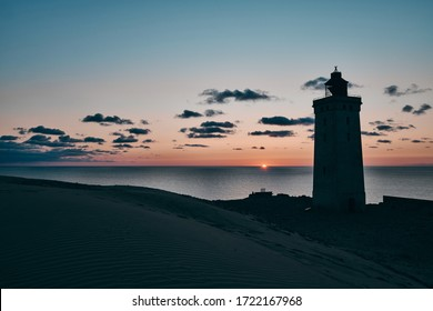 Landscape of lonely sandy seashore and rocked lighthouse under beautiful colorful heaven at dusk