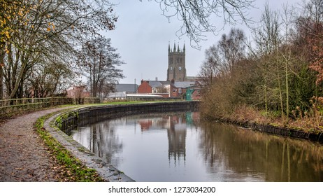 A landscape looking down a canal at a church spire in the distance. The canal bank curves leading to the spire
