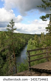 A landscape from a lookout. In front, there is a wooden fence. In the background, there is the lake, forest and blue sky with cumulus clouds. The photo is from Helvetinkolu lookout in Finland.