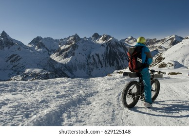 Landscape: man with ebike - mountain bike with electric battery and snow-covered wheels, climbing in high mountains with ski loaded on bike, winter, Riale, Formazza valley, Alps, Italy