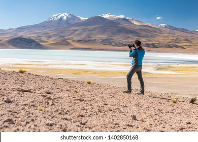 Landscape man photographer taking photos in an amazing wilderness environment at Atacama Desert Andes mountains lagoons. A man cut out silhouette over the awe Tuyajto Lagoon scenery at Altiplano