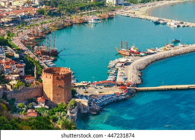 Landscape with marina and Kizil Kule tower in Alanya peninsula, Antalya district, Turkey, Asia. Famous tourist destination with high mountains. Part of ancient old Castle. Summer bright day