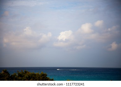 Landscape of the Mediterranean coast with a bush in the foreground, a boat in the background and expressive clouds in the blue sky