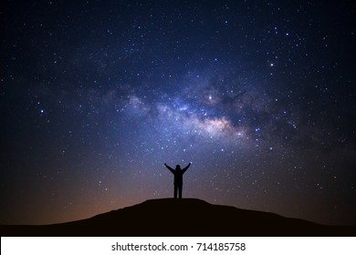 Landscape with milky way galxy, Night sky with stars and silhouette of happy man standing on high moutain