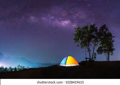 Landscape of Milky Way in night sky over mountain. Small Yellow Camping Tent Picnic Illuminated on top mountain, Recreation and outdoor travel concept