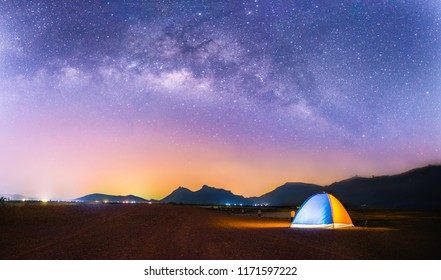 Landscape of Milky Way in night sky over mountain. Small Yellow and Blue Camping Tent Picnic Illuminated on top mountain, Recreation and outdoor travel concept